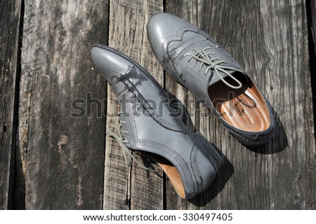 Damaged old grey brogue shoes which made from leatherette on wood back ground