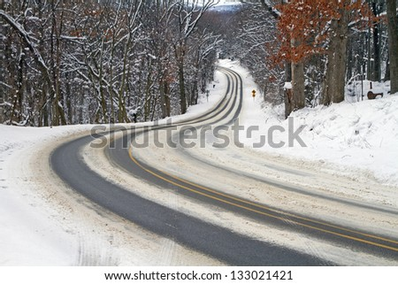"""Dangerous Curves"" -- The winter provides a test for winter driving as a curvy road winds downhill. - stock photo"