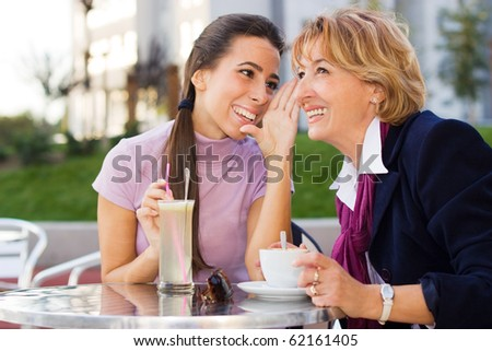 Daughter and Mother chatting in Cafe outdoors. - stock photo