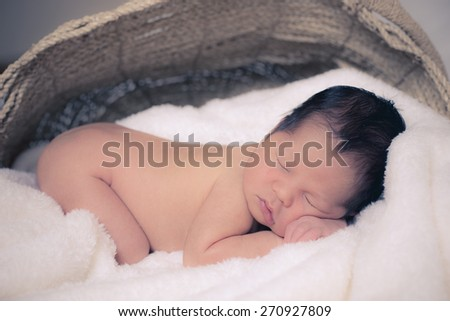 5 day old mixed race Asian Caucasian newborn baby boy sleeps peacefully on thick soft blankets. - stock photo