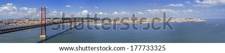 25 de Abril Bridge in Lisbon, Portugal. Connects Lisbon and Almada cities crossing the Tagus River. View from Almada city with Lisbon across the river. - stock photo