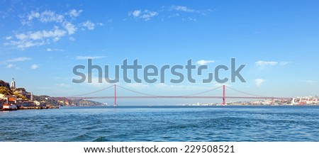 25 de Abril Bridge in Lisbon, Portugal. One of the largest suspension bridges in the world. Connects Lisbon and Almada cities crossing the Tagus River - stock photo