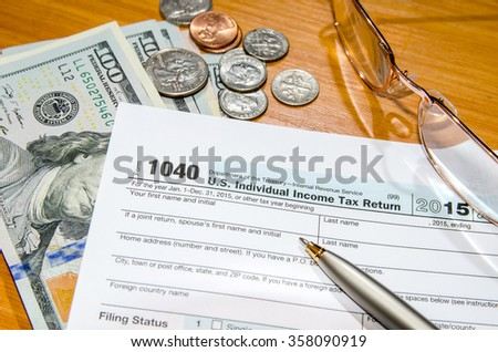 deadline time of 1040 tax form for 2016 with dollar and pen