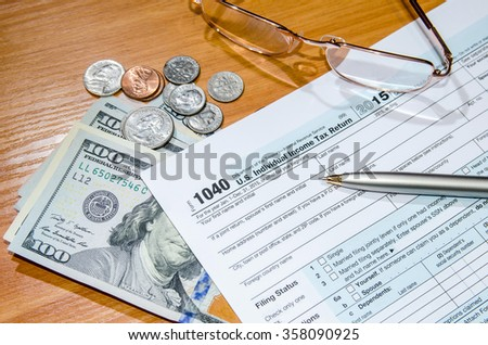deadline time of 1040 tax form for 2016 with dollar and pen - stock photo