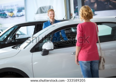 Dealer showing a new car model to the potential customer - stock photo