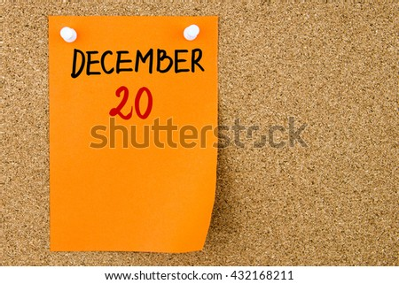 20 DECEMBER written on orange paper note pinned on cork board with white thumbtacks, copy space available - stock photo