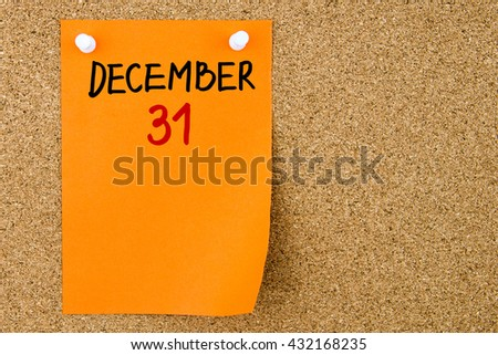 31 DECEMBER written on orange paper note pinned on cork board with white thumbtacks, copy space available - stock photo