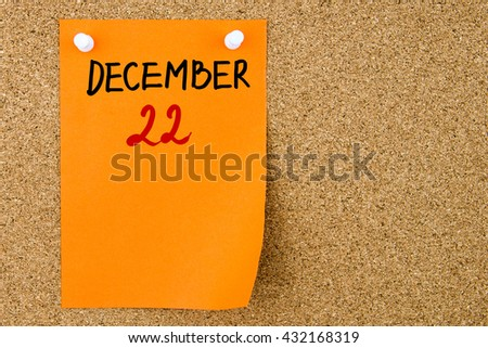 22 DECEMBER written on orange paper note pinned on cork board with white thumbtacks, copy space available - stock photo