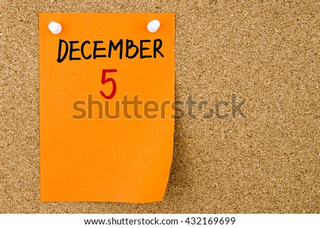 5 DECEMBER written on orange paper note pinned on cork board with white thumbtacks, copy space available - stock photo
