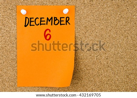 6 DECEMBER written on orange paper note pinned on cork board with white thumbtacks, copy space available - stock photo