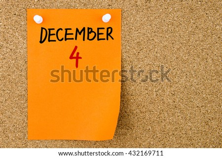 4 DECEMBER written on orange paper note pinned on cork board with white thumbtacks, copy space available - stock photo