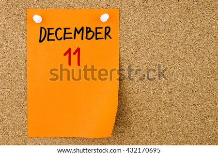 11 DECEMBER written on orange paper note pinned on cork board with white thumbtacks, copy space available - stock photo