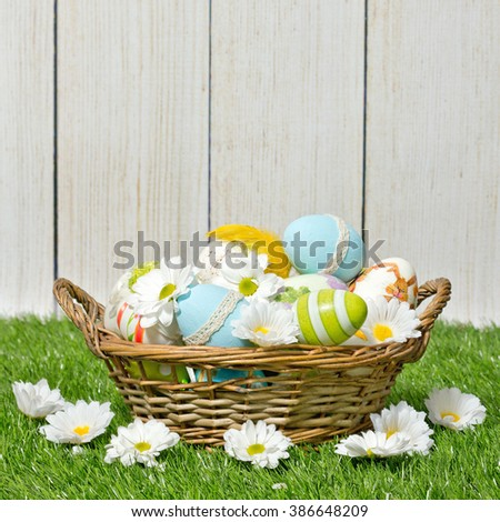 decorated easter eggs in the basket on wooden background