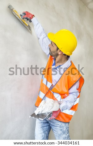 Decorative plaster applied on the surface by a steel trowel. White cement based decorative top coat plaster resistant on outside whether conditions. Selective focus. Gypsum Workers . - stock photo