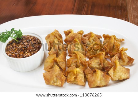 Deep fried pork dumplings with sweet and spicy sauce a white plate.