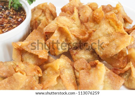 Deep fried shrimp dumplings with sweet and spicy sauce a white plate.