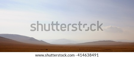 delicate haze of morning mist over the valley. hilly landscape. Savannah, grassland . used toning of the photo - stock photo