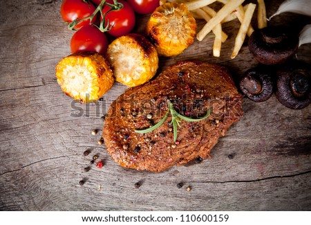 Delicious beef steaks on wooden table, up view - stock photo
