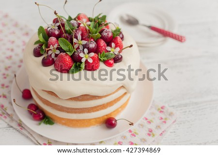 Delicious biscuit cake with strawberries and cherries on wooden background - stock photo