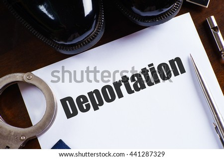 """""""Deportation"""" text on paper with pen, whistle, handcuff and a pair of black shoes on wooden table - law and enforcement concept - stock photo"""