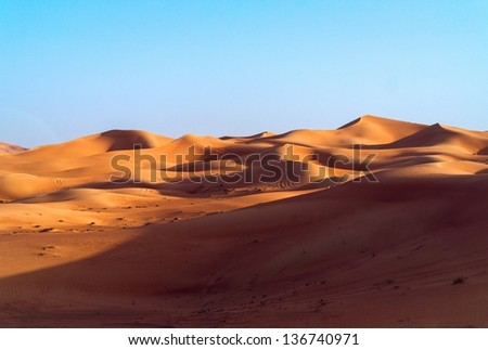 desert dune background on blue sky. Arabian desert near the city of Dubai. Mountains and hills of colored sand - stock photo