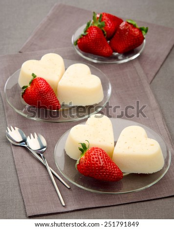 dessert for lovers blanc-mange with strawberries in the form of heart on a transparent plate - stock photo