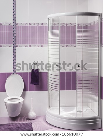 detail of a modern bathroom interior with luxury shower and toilet with purple and white tiles - stock photo
