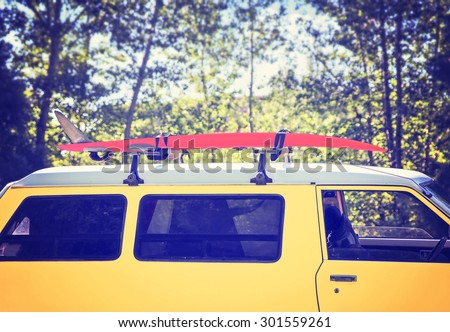 Detail of a vintage camping van in the forest with a surfboard on the roof toned with a retro vintage instagram filter app or action effect - stock photo