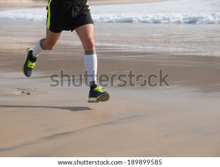 Detail of the legs of an athlete running on the beach outdoors