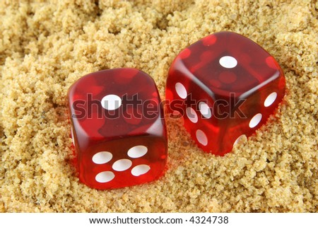 2 Dice showing snake eyes - half buried in the sand