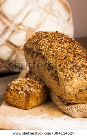 Different kind of breads placed on the wooden cutting board.  - stock photo