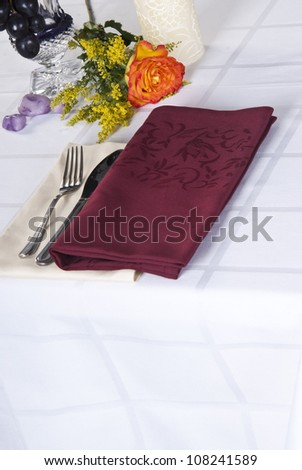 Dining table set on white bad linen. - stock photo