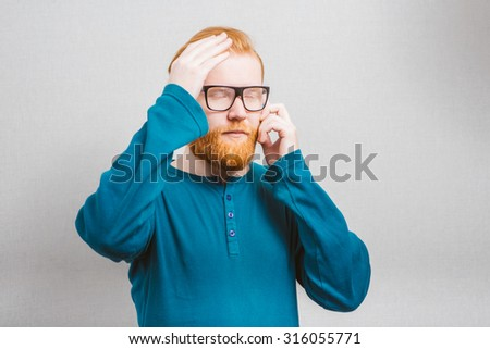 disappointed man with glasses talking on the phone - stock photo