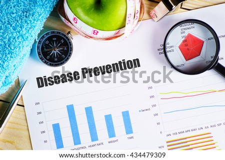 """""""Disease Prevention"""" black text on paper with magnifying glass on red spider bar on wooden table with compass, green apple with measurement tape, and whistles - fitness, diet and healthy concept - stock photo"""