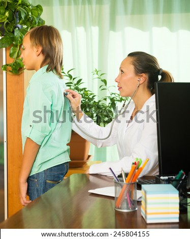 doctor with stethoscope examining teenage boy in clinic office - stock photo