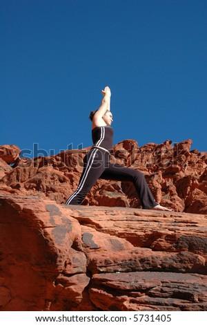 Doing yoga on red rocks - stock photo