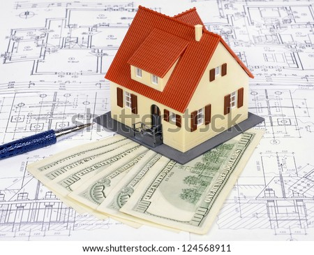 dollar banknotes and a model house on a construction plan for house building; concept of buying a house - stock photo