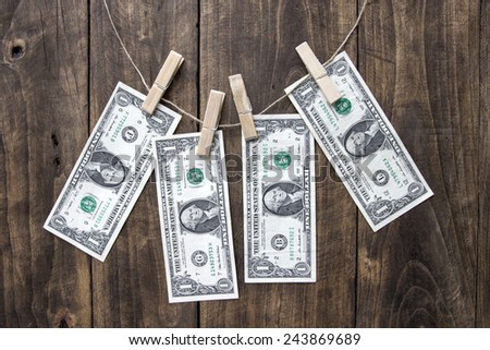 Dollar bills hanging on rope attached with clothes pins. - stock photo