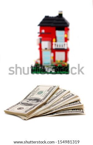 100 dollar bills on a white background, in the background a little house - stock photo