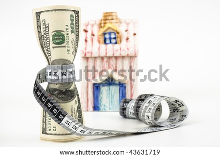 100 dollar bills tight with a measuring tape a small house in the background white background - stock photo