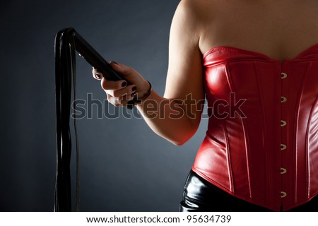 DOMINATRIX in red leather corset with black whip - stock photo