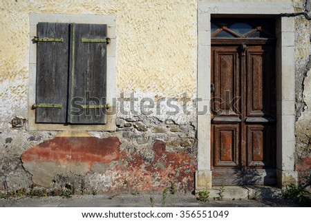 Door and window of old stone house on the street in France