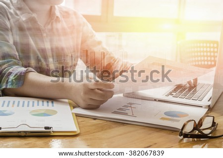 Double exposure of male business mant sitting at wooden desk and using digital computer while typing something on keyboard,freelancer working with laptop,flare light,selective focus,vintage color - stock photo