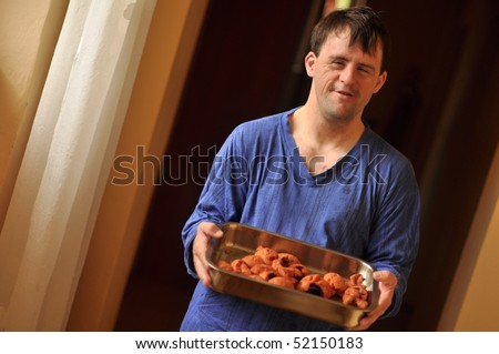 down syndrome man holding meat fillet - stock photo