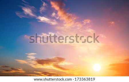 Dramatic sunset sky with orange colored clouds and sun. - stock photo