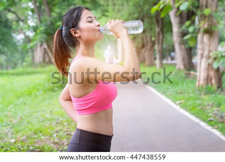Drinking water after workout.Women exercising in a park. Portrait Female jogger. Fit young Asian woman jogging in park smiling happ. - stock photo