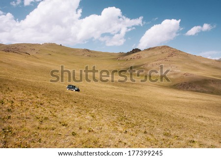 Dry grass hill with auto drive down in the mountains of Central Asia at the bright sunny day - stock photo