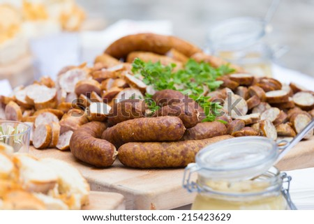 Dry sausage cold cuts. A variety of dry cold smoked meat products with herbs and mustard and  horseradish spreadon a wooden cutting board.  - stock photo