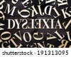 ''Dyslexia'' word with wooden letters on dark background - stock photo