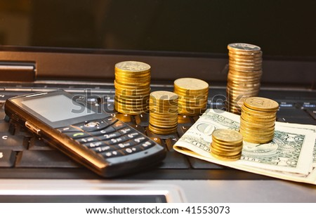 E-commerce. Mobile phone, bills and coins on laptop keyboard - stock photo